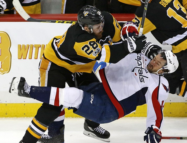 Pittsburgh Penguins' Ian Cole (28) checks Washington Capitals' Justin Williams (14) off the puck during the third period of Game 4 Wednesday, May 3, in Pittsburgh. (Gene J. Puskar/AP)
