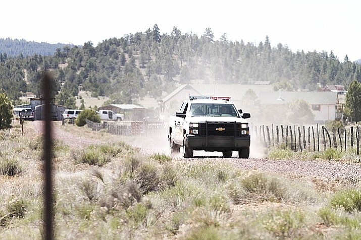A Coconino County Sheriff's deputy leaves the scene of a double homicide in the Red Lake area north of Williams May 3.