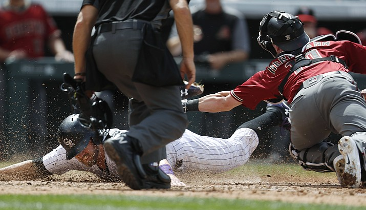 Colorado's Mark Reynolds, left, slides safely into home to score on a Trevor Story double as Diamondbacks catcher Chris Herrmann applies a late tag during Sunday's baseball game in Denver.