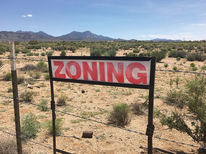 "A ""zoning"" sign stands on Paradise Avenue near Sage Street, with 35 acres behind it planned for Paradise Estates subdivision by Angle Homes. The City Council denied a plat request by home builder Doug Angle that would exempt him from putting in sidewalks, curbs and gutters."