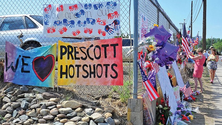 People look and add items to the memorial to the 19 Granite Mountain Hotshots outside of Station 7 in days following the deaths of 19 firefighters.
