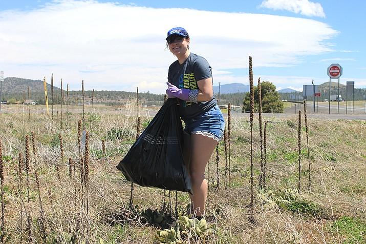 Williams High School student Arianna Foley picks up litter.