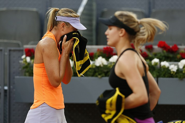 Maria Sharapova from Russia, left, wipes the sweat from her face as Eugenie Bouchard from Canada walks past her during a Madrid Open tennis tournament match in Madrid, Spain, Monday, May 8, 2017. Bouchard won 7-5, 2-6 and 6-4. (Francisco Seco/AP)