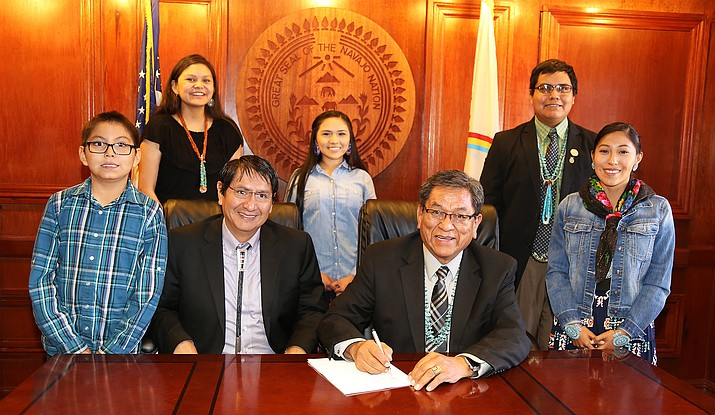 President Russell Begaye signs youth council legislation into law alongside Virlencia Begay, Cali Chee, Marlon Murphy, Jacquelyn Johnson, Vice President Jonathan Nez and Christopher Nez. Submitted photo