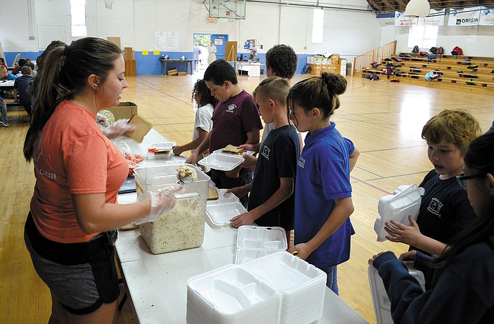 Boys and Girls Club staff member Brooke Huffer (left) serves up tuna salad to some hungry kids.