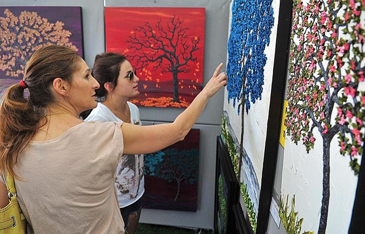 Joan Bucklew, left, and her daughter Shelby Mazon of Las Vegas check out the oil paintings of Carla Wright of Denver Saturday afternoon during the 26th Annual Mountain Artists Guild Fine Art and Wine Festival in downtown Prescott.