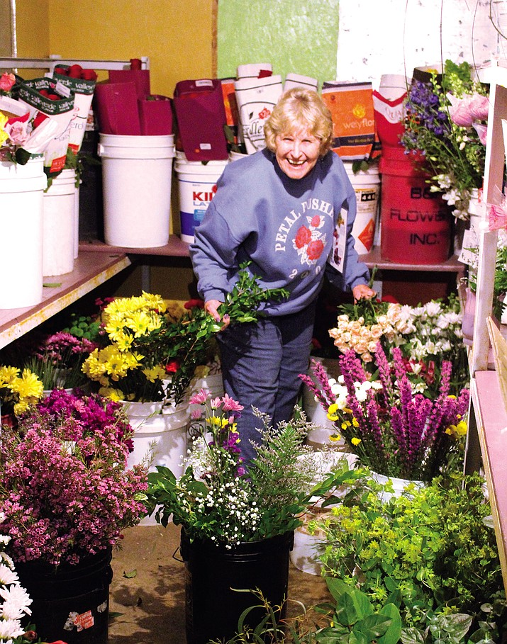 Carole Gallagher retrieves flowers kept in the cooler at Heaven's Scent Florist in Kingman.