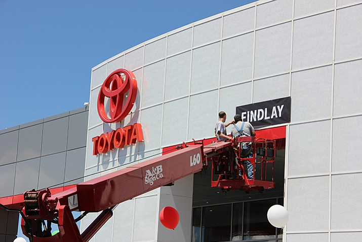 Workers with A&B Sign Co. replace Tim's Auto Group signage with Findlay Automotive Group signage following a sale of the business. (Max Efrein/Courier)
