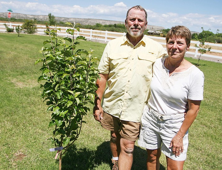 Doug and Christie Fasteen stand in their Camp Verde garden with one of their honey crisp apple trees. (Photo by Bill Helm)