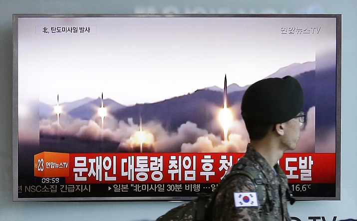 A South Korean army soldier walks by a TV news program showing a file image of missiles being test-launched by North Korea, at the Seoul Railway Station in Seoul, South Korea, Sunday, May 14.