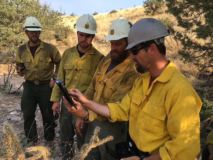 Firefighters operate a drone near a recent wildfire. The drones allow the crew to view the fire's progress in real time from a safe distance.