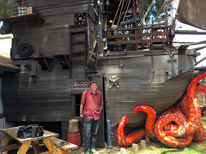 """Steven Hill poses with the three-story pirate ship he built in the backyard of his Casa Grande, Ariz., home. He's become the neighborhood pirate with his replica of the """"Pirates of the Caribbean"""" Black Pearl. (Melissa St. Aude/Casa Grande Dispatch via AP)"""