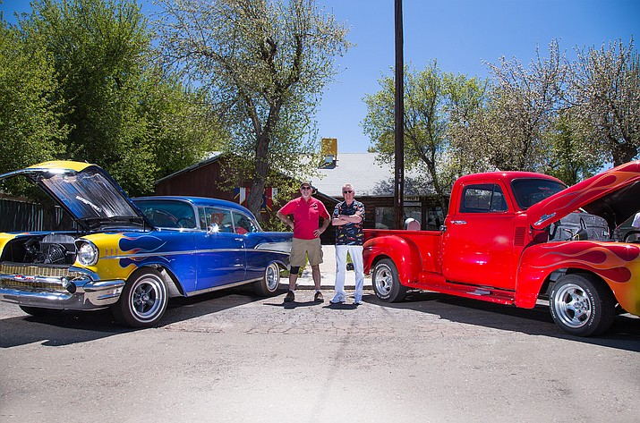 American Legion Cordova Post No. 13 members John Holst and Rodger Ely stand in front of the Legion Post between two classic cars.