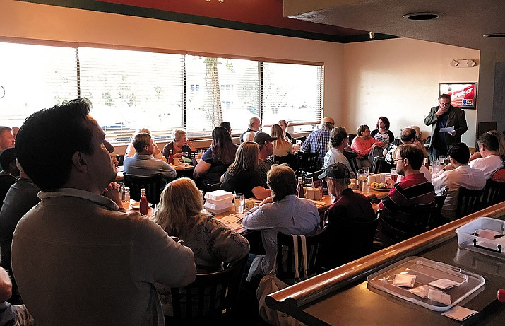 Pilot and airport business owner Paul Gaines (far right, standing) discusses ways to take on the Kingman Airport Authority to a packed house at Calico's Monday night.