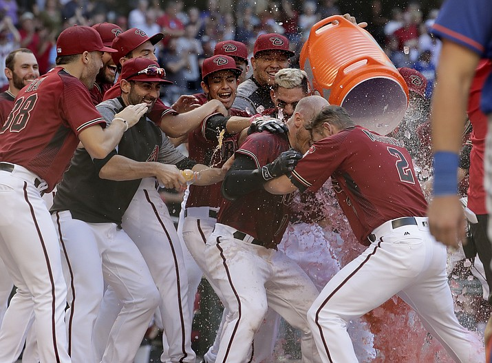 Arizona Diamondbacks Chris Herrmann, center, celebrates his walk-off home run during the 11th inning of a baseball game against the New York Mets on Wednesday, May 17, 2017, in Phoenix. The Diamondbacks won 5-4. (Matt York/AP)