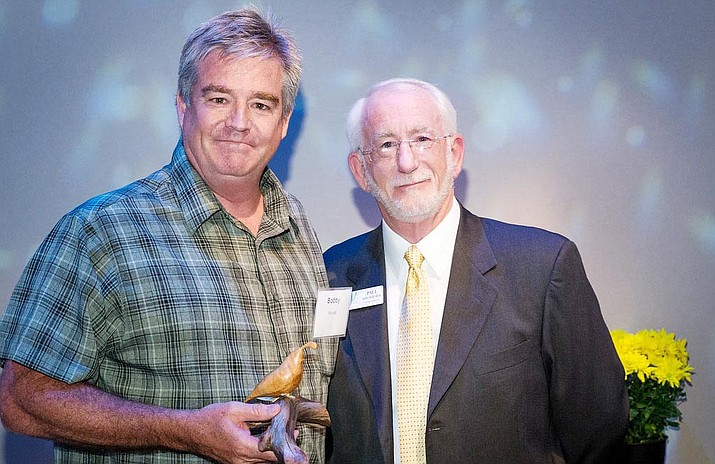 Cottonwood resident Bobby Woods, left, receives the Yavapai College Foundation's Outstanding Volunteer Award for helping raise funds and awareness of the college's programs in the Verde Valley. Presenting the award, Paul Kirchgraber, the foundation's executive director. (Courtesy photo)