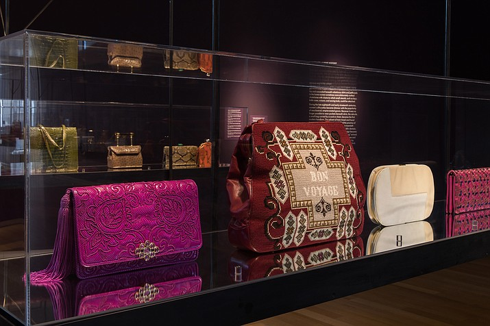 """This undated photo provided by the Museum of Arts and Design shows a display case that includes a 1973 fuchsia bag featuring embroidery, and one of the larger scale bags, a 1980 travel bag featuring """"gros point"""" needlepoint embroidery. Also on view are a white handbag from the 1970s and a small fuchsia bag made of leather and suede in a woven pattern made in 1977. It is part of an installation view in the exhibit """"Judith Leiber: Crafting a New York Story."""" (Jenna Bascom/Museum of Arts and Design via AP)"""