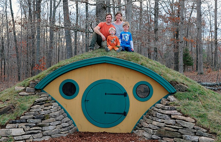 Rocy and Melissa Pillsbury and their children sit atop a custom Hobbit House in Santa Fe, Tennessee. (Jonathan Giffin via AP)
