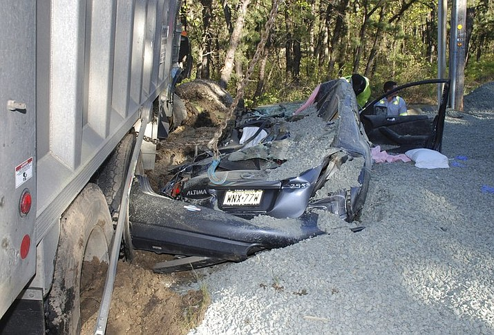 A car is covered with gravel after a dump truck overturned in Manchester, N.J., and spilled its load. Police said that 24-year-old Andrea Penna, of Whiting, N.J., was trapped underneath stone and debris after the roof of her car collapsed on top of her. (Township Police Department via AP)