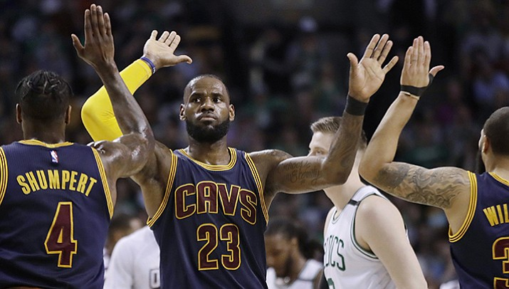 Cleveland Cavaliers forward LeBron James trades high-fives with teammates Iman Shumpert, left, and Deron Williams, right, during the first half of Game 2 of the NBA basketball Eastern Conference finals against the Boston Celtics, Friday, May 19, in Boston.