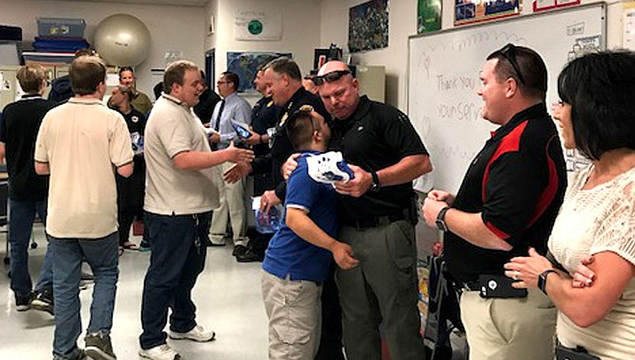 Kingman Police, including Sgt. Mike Godfrey and his 11th-grade son, Tanner (center, hugging), meet and greet with Kingman Academy High School students.