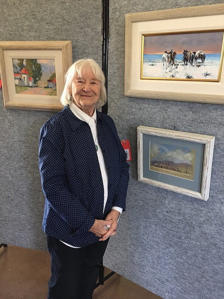 Bonnie Casey stands next to some of her paintings at the Smoki Museum in Prescott