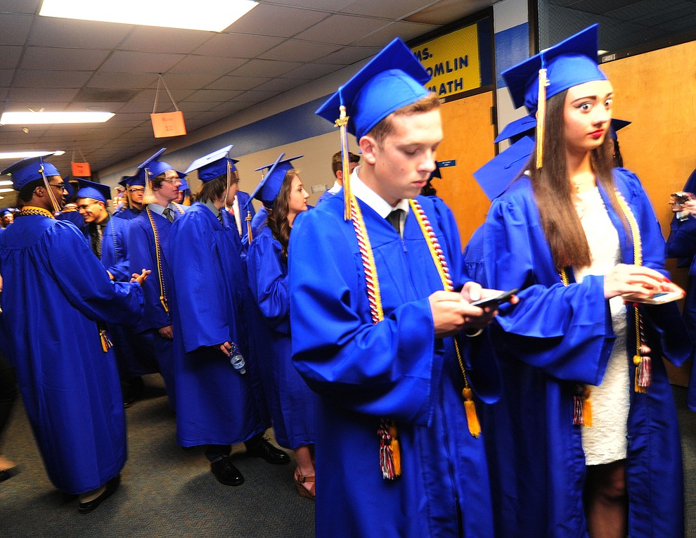 Keith Bunn and Carlee Votava get some last minute texting in before the 345 members of the Prescott High School Class of 2017 held their Commencement on Bill Shepherd Field Friday, May 26. (Les Stukenberg/Courier)