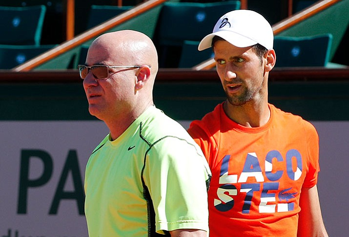 Defending champion Serbia's Novak Djokovic watches Andre Agassi, left, of the U.S, during a training session for the French Open tennis tournament at the Roland Garros stadium, Friday, May 26, in Paris. Agassi is Djokovic's new coach. (Christophe Ena/AP)
