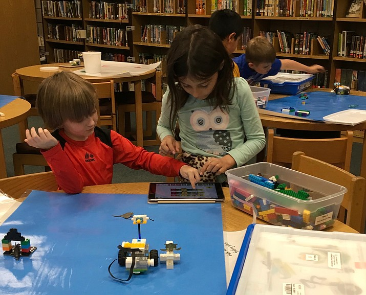 Beginning robotics first-grader Seamus Smith and second-grader Gwen Herbert program the robot they built to discover undersea animals. The robot moves, uses a motion sensor, flashes lights, makes sounds, shows displays, and plays the recordings they've created.