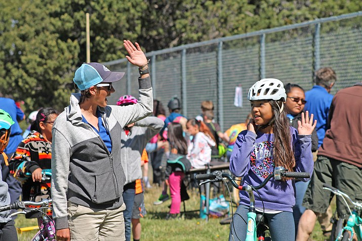 A student learns proper biking hand signals from a Bright Angel Bikes staff member before taking on the obstacle course.