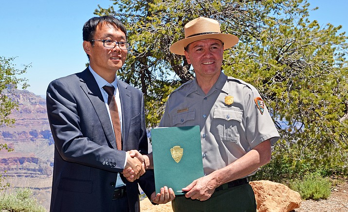 Jin Guibin, Yuntaishan Geopark's director and Brian Drapeaux, deputy superintendent of Grand Canyon National Park, pose for a photo after renewing their Sister Park agreement.