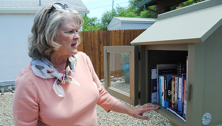 Victoria Clark counts the number of books inside Cottonwood's Old Town Little Free Library. Cottonwood's Old Town Little Free Library is located 802 N. Main St., Old Town, next to Crazy Tony's. (VVN/Jennifer Kucich)