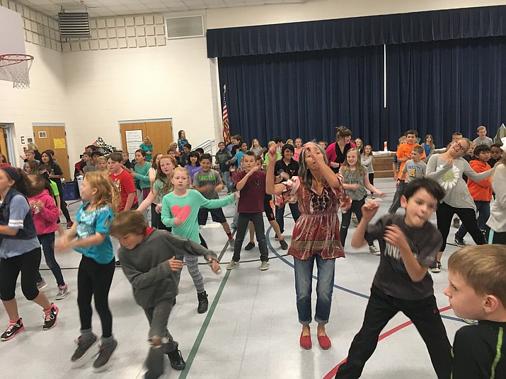 "Ms. Daniele Rosellini, fourth-grade teacher at Abia Judd Elementary School, leads her students in a ""flash mob"" dance celebrating their success at the recent Abia Judd Poetry Palooza."