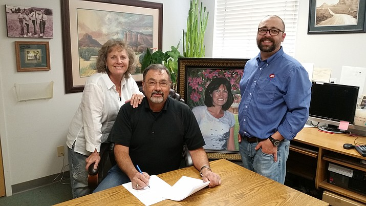Leann Weber (left) and Jake Weber sign the paperwork to finalize sale of the Weber's IGA market to the Clark family of Aspen, Colorado, along with their son Josh and a portrait painting of their daughter Lisa. Photo courtesy of Stacey L. Beck.