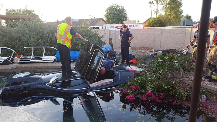 Fire and police first responders rescued an elderly man from an SUV before it became fully submerged underwater on its side in a pool in Scottsdale Monday. (Scottsdale Fire Department photo)