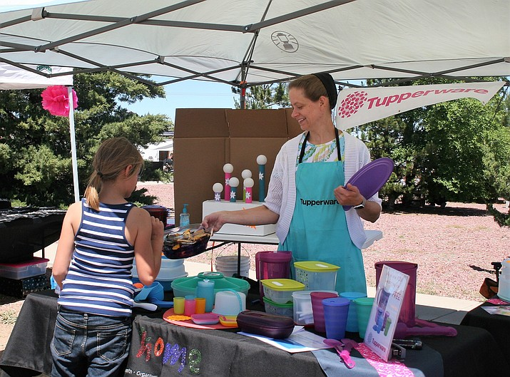 Tupperware winner coming to the booth to pick up their prize at the Heritage Festival in June, a community event staged by the Chino Valley Area Chamber of Commerce.