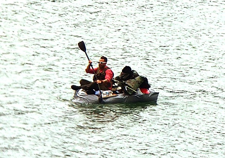 An unidentified man paddles a home made, inflatable, duct-taped boat before being rescued by a smallboat crew after his craft began taking on water in Gastineau channel near Juneau, Alaska, Wednesday, June 7, 2017. The Coast Guard crew deemed the craft unsafe and transferred the man, his dog and the craft to Douglas Harbor in Juneau. (U.S. Coast Guard via AP)