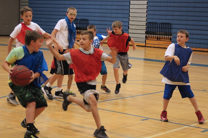 Reiley King, left, looks for an open teammate during a basketball camp Thursday at Kingman High School.