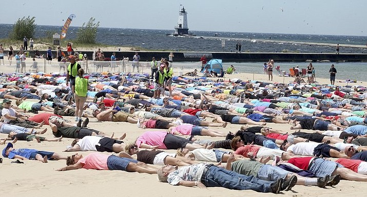 Around 1,387 take part in an attempt to break the Guinness Book record for simultaneous sand angels on Saturday, June 10, 2017 in Ludinton, Mich. (Jeff Kiessel/Ludington Daily News via AP)