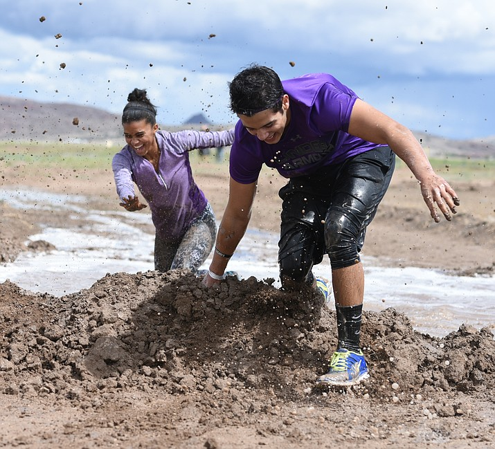 Caitlyn Ballard and Brandon Celaya make it through a mud pit during a previous Chino Mudder. This year's event is set for Aug. 26. (Les Stukenberg/Courier)