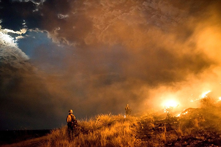 This photo provided by the Wyoming Hot Shots, members of the Wyoming Hot Shots firefighting crew watch the moon break through smoke and clouds while battling the Lizard Fire near Willcox, AZ, June 8. Thousands of firefighters continue to battle almost 30 wildfires burning throughout Arizona as gusty winds and dried vegetation continue to fuel the blazes. (Kyle Miller/Wyoming Hot Shots via AP)