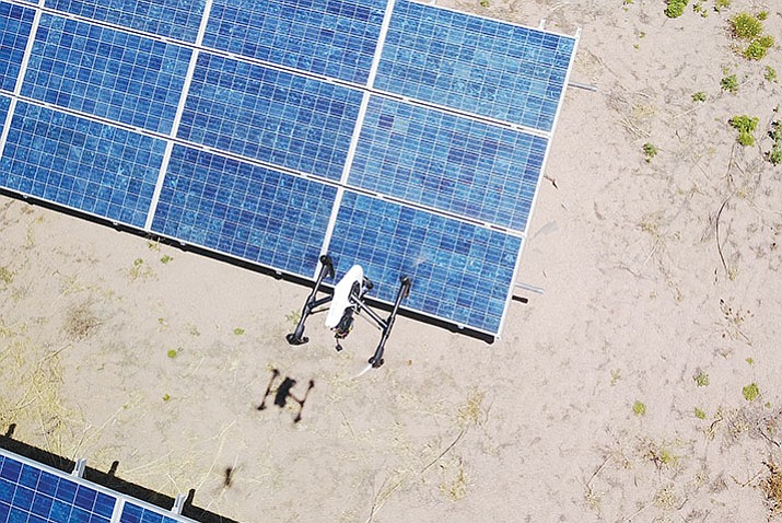 A photograph of a drone checking solar panels is taken by a second drone. Drones that carry cameras can cut inspection times, for instance, from days down to minutes. (Karl Costitch/Courtesy)