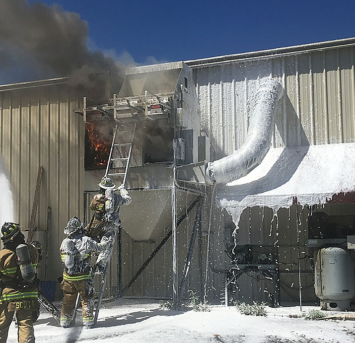 Prescott firefighters work to put out a fire in a defective sawdust collection unit Friday at a business on EZ Street in Prescott. (Prescott Fire Dept./Courtesy)