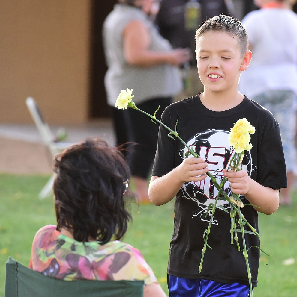 Elijah Brewster hands out yellow carnations during a candlelight vigil in honor of ten-year-old Christian Pearson at Memory Park in Chino Valley  Saturday, June 17. (Les Stukenberg/Courier)