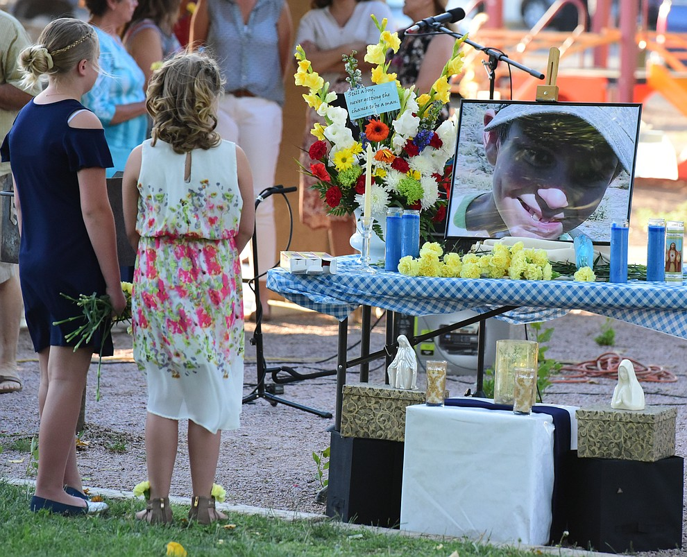 Hannah Myers and Kayla Choate look at the memorial to their friedn Christian during a candlelight vigil in honor of ten-year-old Christian Pearson at Memory Park in Chino Valley  Saturday, June 17. (Les Stukenberg/Courier)