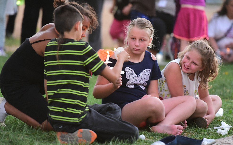 Close friends light their candles despite a steady breeze during a candlelight vigil in honor of ten-year-old Christian Pearson at Memory Park in Chino Valley  Saturday, June 17. (Les Stukenberg/Courier)
