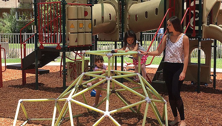 Children at the Child Study Lab Preschool play on the playground with an undergraduate research student, Sarah Giedraitis, during break time.