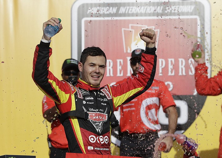 Kyle Larson raises his arms after exiting his car after winning a NASCAR Sprint Cup series auto race, Sunday, June 18, 2017, in Brooklyn, Mich. (Carlos Osorio/AP)