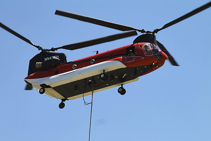 A CH-47 Chinook twin-engine, tandem rotor heavy-lift helicopter drops a bucket into Santa Fe Dam reservoir June 12 to assist with the June 12 wildfire in Williams.