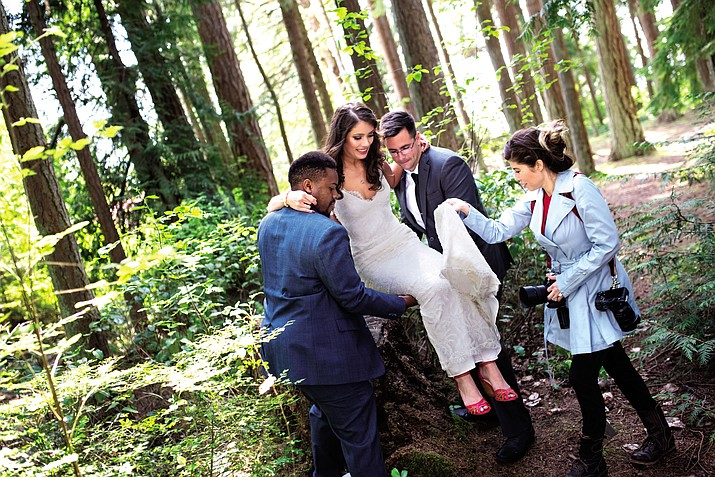 JoAnne Marino helps a bride keep her dress clean during a wedding photo shoot in the forests of Bainbridge Island off the coast of Seattle.